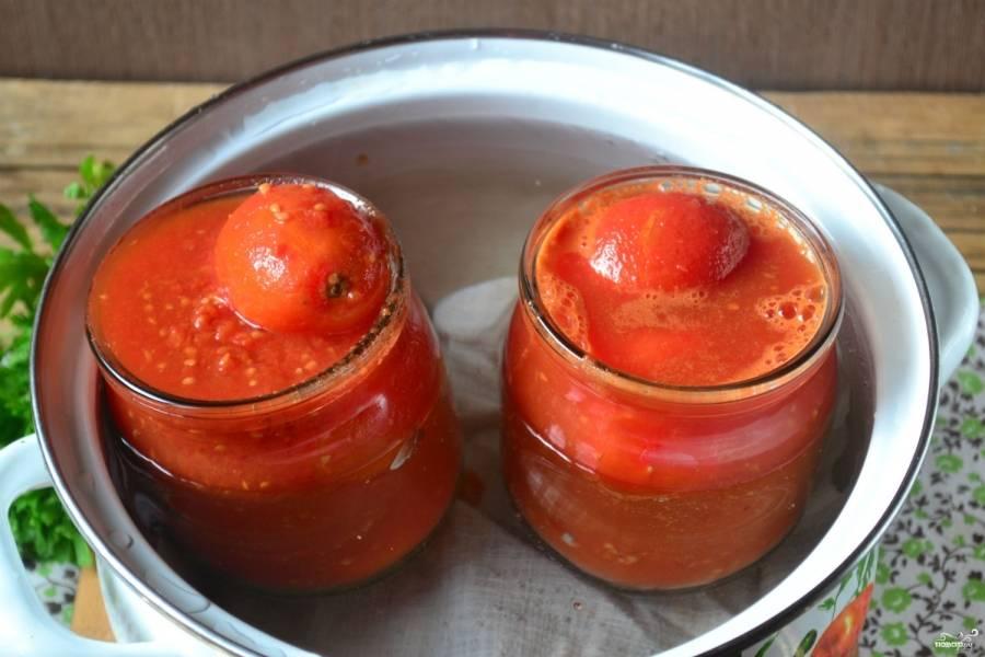 Залейте помидоры томатным соком, прикройте банки металлическим крышками, стерилизуйте 10-12 минут. Затем банки закатайте и укутайте.