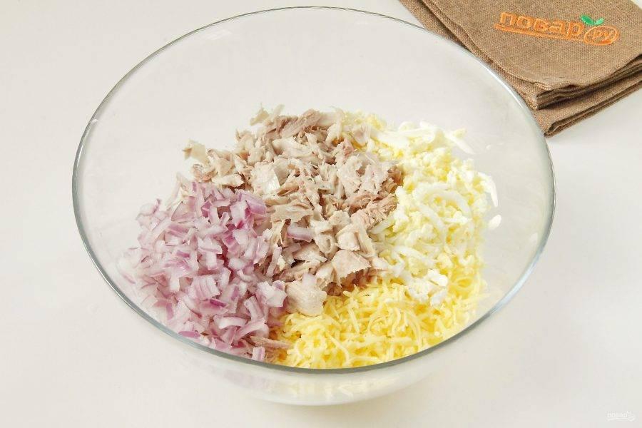 В глубокой миске соедините нарезанное филе, тертые яйца, сыр (немного оставьте для украшения) и отжатый от воды лук.