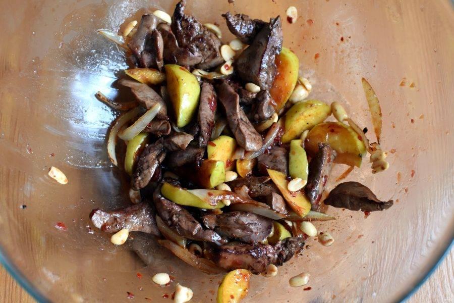 Теплую печень выложите в миску к яблокам и луку. Добавьте арахис и полейте соусом. Легко перемешайте двумя ложками, старясь не помять яблочные дольки.