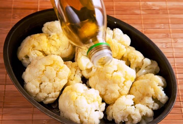 Цветную капусту отварите до полуготовности, затем разберите на соцветия и выложите в форму для запекания. Полейте растительным маслом и отправьте в духовку на 10 минут при 200 градусах.