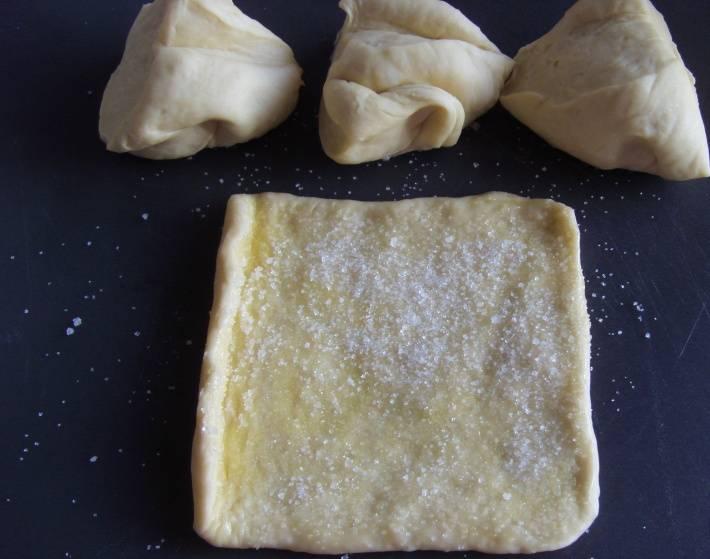 Перед тем как начать делать будущие булочки, ещё разок вымесим тесто. Затем разделим его на небольшие части (у меня получилось 8), раскатываем. Смазываем каждую часть растопленным сливочным маслом и посыпаем сахаром.