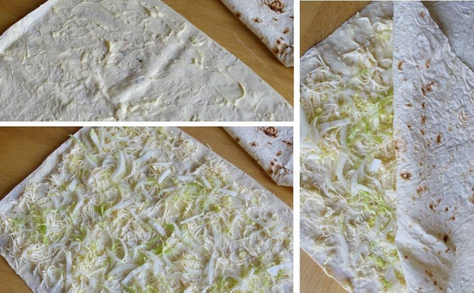 Рулет будет состоять из двух слоев лаваша с начинкой.  Возьмите первый лаваш, смажьте его майонезным соусом с чесноком. Затем равномерно выложите на него тертый плавленый сыр и половину нашинкованной пекинской капусты. Теперь положите второй лаваш, плотно прижмите его к первому слою.