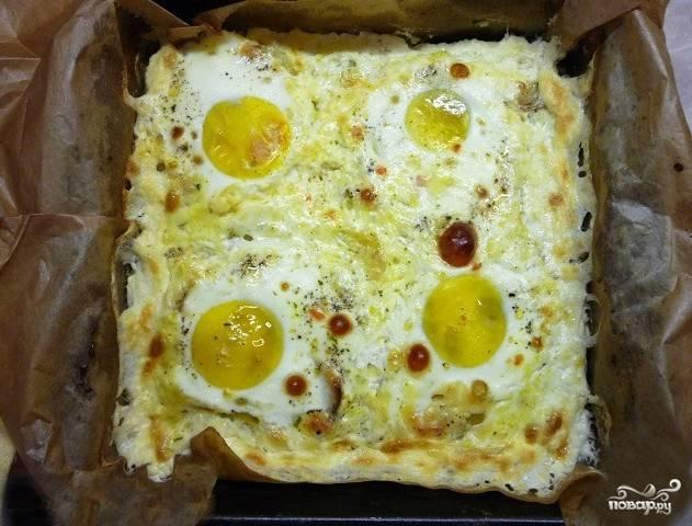 Ставим блюдо запекать в духовку на 15 минут при 180 градусах. Зависит от того, насколько вы хотите, чтобы поджарились яйца. Вытаскиваем по готовности. Все отлично запеклось. Подавайте с овощами и рыбными консервами. Приятного аппетита!