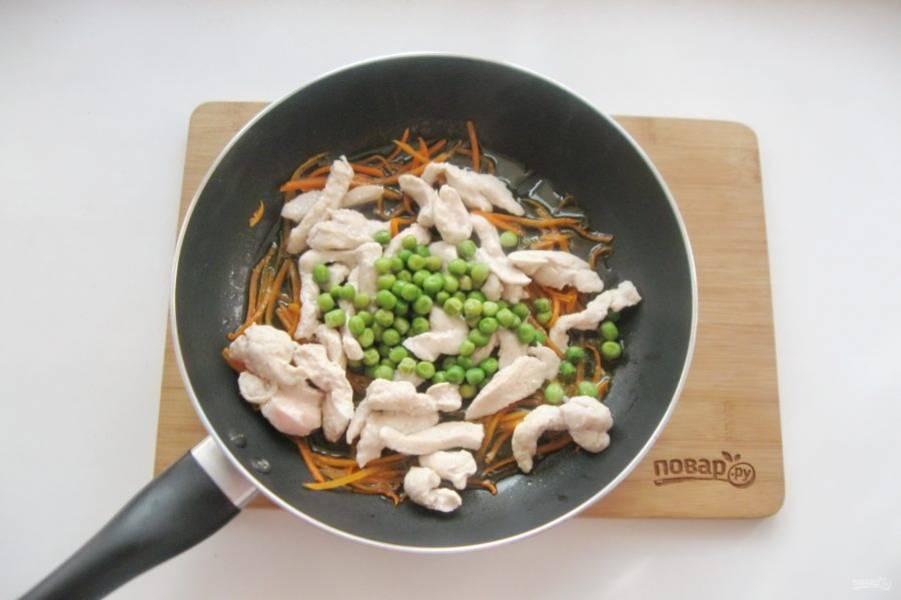 Выложите зеленый горошек. Налейте 50 мл. воды, накройте крышкой и тушите морковь с курицей и горошком 5-6 минут.
