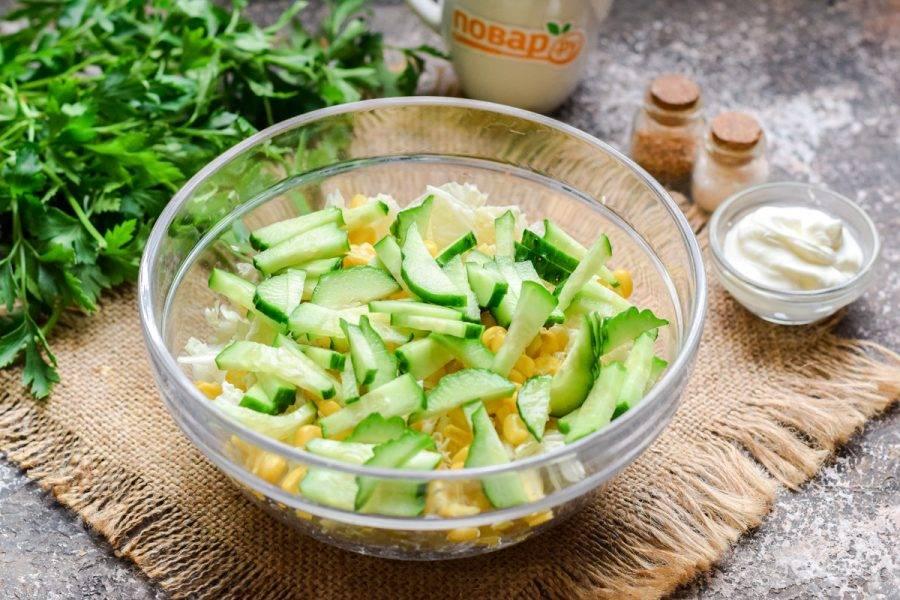 Свежий огурец нарежьте небольшими полосками. Добавьте огурцы в салат.