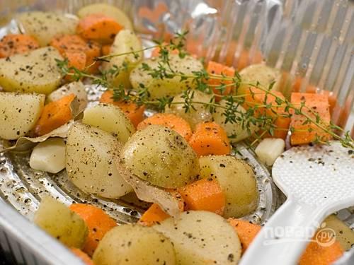 3. В лотке для выпекания смажьте нарезанный на кубики картофель и морковь столовой ложкой масла. Приправьте солью и перцем. Добавьте тимьян и сок лимона.