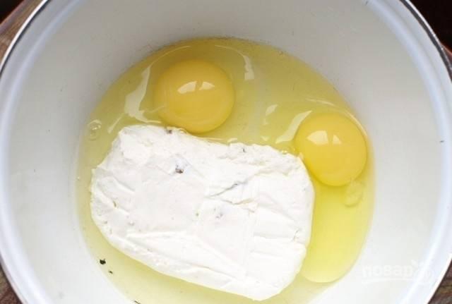 Разотрите вилкой в глубокой миске творог с яйцами.