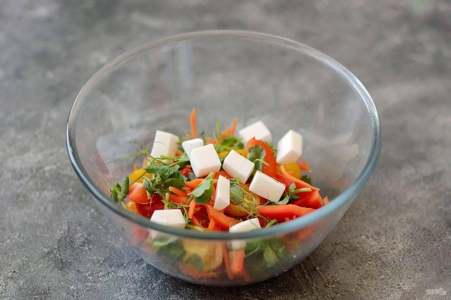 Переложите овощи в миску. Добавьте нарезанный кубиками сыр и ростки гороха.