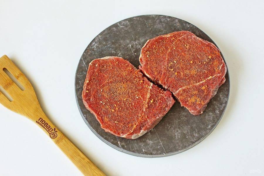 Готовые стейки отбейте специальным молоточком с двух сторон, натрите солью и специями.