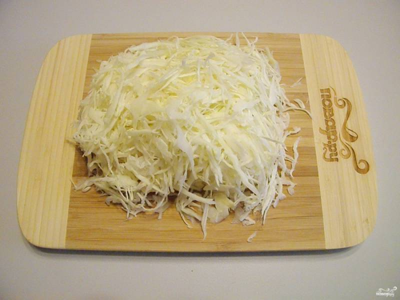 Нашинкуйте тонко капусту.