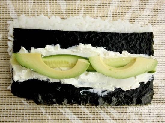Теперь выложим сливочный сыр, а на него — брусочки очищенного авокадо и огурца.