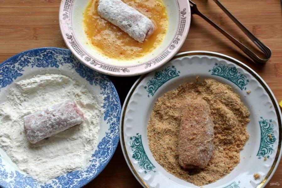 Приготовьте панировочную линию, насыпав в тарелки муку и просеянные молотые сухари. Каждый рулетик обваляйте сначала в муке, а затем полностью обмакните в яйцо и запанируйте в сухарях.