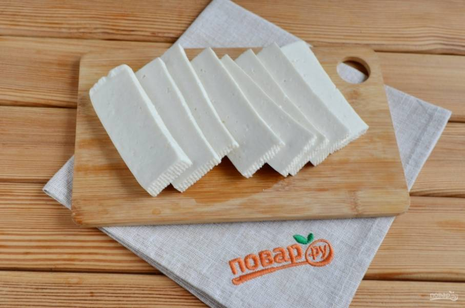 Порежьте сыр острым ножом на пластинки. Толщина сыра от 0,5 до 1 см.