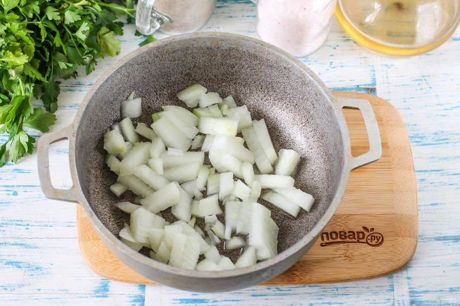 Лук нарежьте мелкими кубиками. Прогрейте в казане или в сотейнике растительное масло и выложите в него луковую нарезку. Обжарьте примерно 3-4 минуты до румяности и мягкости без добавления грибов.