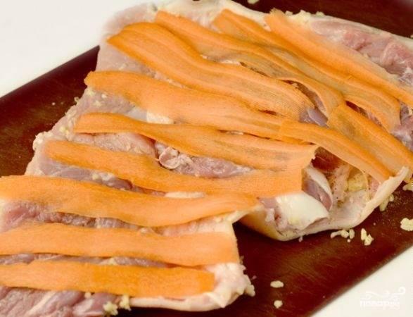 4. Рульку немного отбиваем, чтобы была помягче. Морковь очищаем и нарезаем тонкими пластинками, равномерно распределяем по свинине.