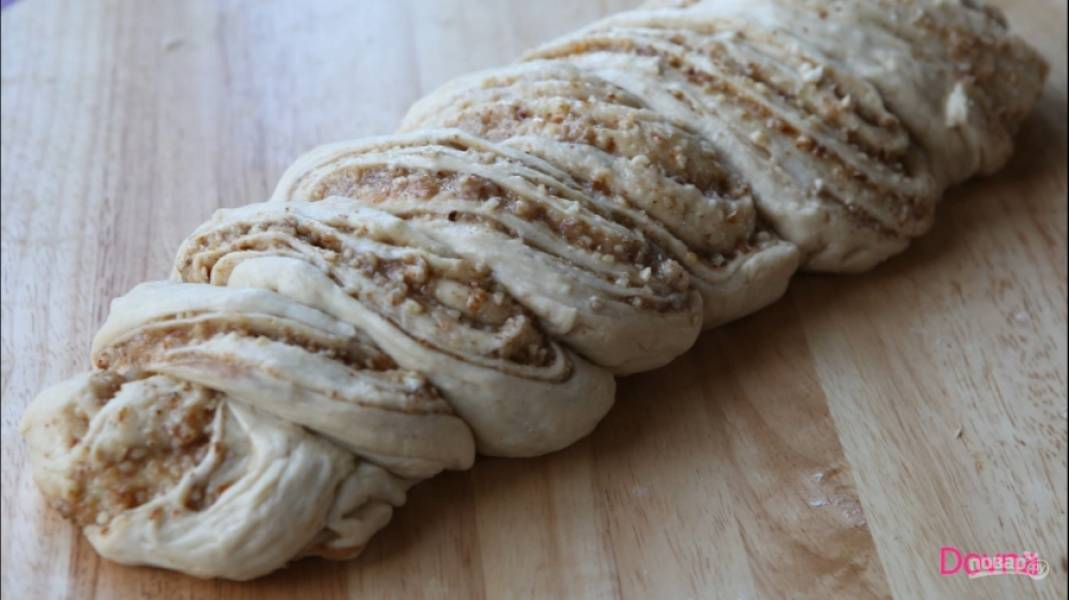 5.Когда тесто подойдет, обомните его и раскатайте в пласт. Сверху распределите начинку. Сверните тесто по продольной стороне, разрежьте его вдоль пополам. Обе части красиво переплетите.