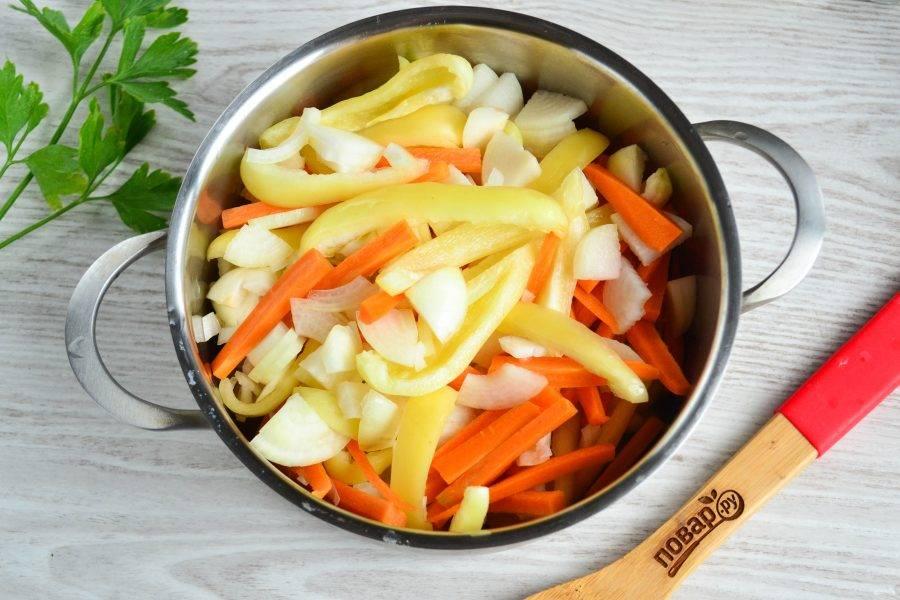 В кастрюлю с толстым дном выложите перчик, морковь и лук.