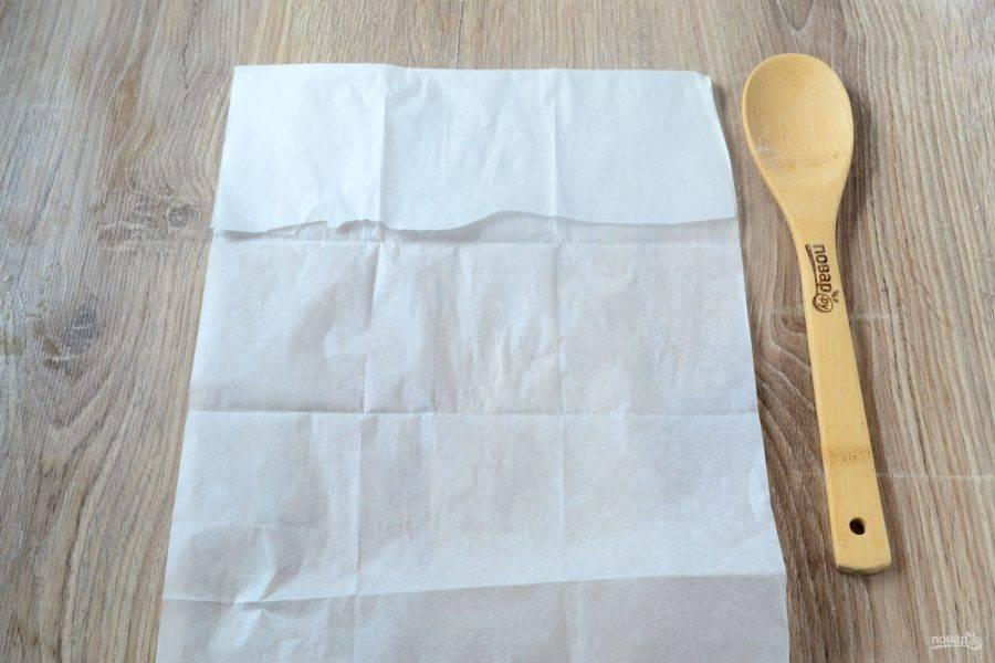 Пока пирожки пекутся, сделайте для них конвертики из пергамента. Для этого возьмите лист пергамента примерно 30х40 см. Положите перед собой вертикально. Сверху примерно 1/5 часть подверните вниз.