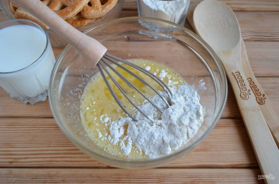 В глубокой посудине соедините венчиком яйца и сахар. Частями всыпайте муку, вливайте стакан молока.