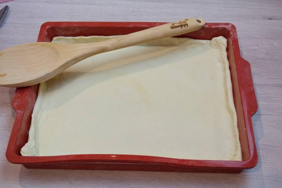 Тесто уложите в форму для выпечки ровным слоем. Силиконовые формы смазывать не обязательно.