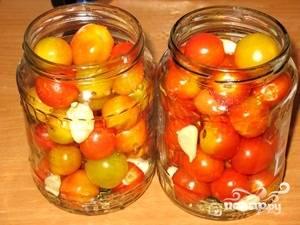 В стерилизованные баночки сложить помидоры, зелень чеснок.