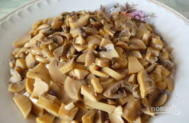 2. Дальше приступим к составлению салата. Первый слой — отварное и мелко порезанное филе. Специи — по вкусу, смажем тонко майонезом. Сверху — слой грибов.