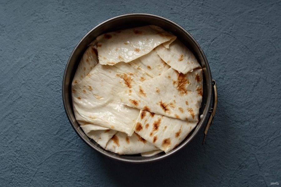 Заверните края лаваша так, чтобы он полностью покрывал диаметр формы для выпечки, лишнее отрежьте. Смажьте верхушку растительным маслом. Выпекайте пирог в духовке 30-35 минут при температуре 170 градусов.