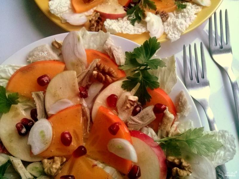 Выложите ингредиенты на тарелку: листья капусты, кусочки индюшиной грудки, хурма, яблоко, маринованный лук, гранат, орехи. Полейте сверху заправкой.