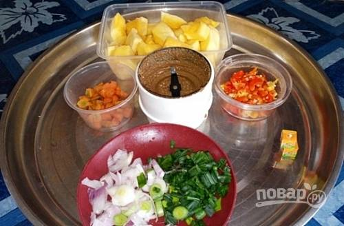 2.Нарежьте тыкву небольшими кубиками, измельчите чили и чеснок, морковь нарежьте небольшими кубиками, луковицу нарежьте крупно. Нарежьте мелко веточки зеленого лука. Обжаренный арахис измельчите в пасту с помощью блендера.