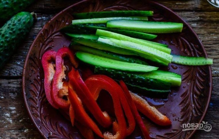 Перец и огурцы вымойте, обсушите. Нарежьте перец полосками, очистите его от семян. Огурцы нарежьте полосками такого же размера, как болгарский перец.