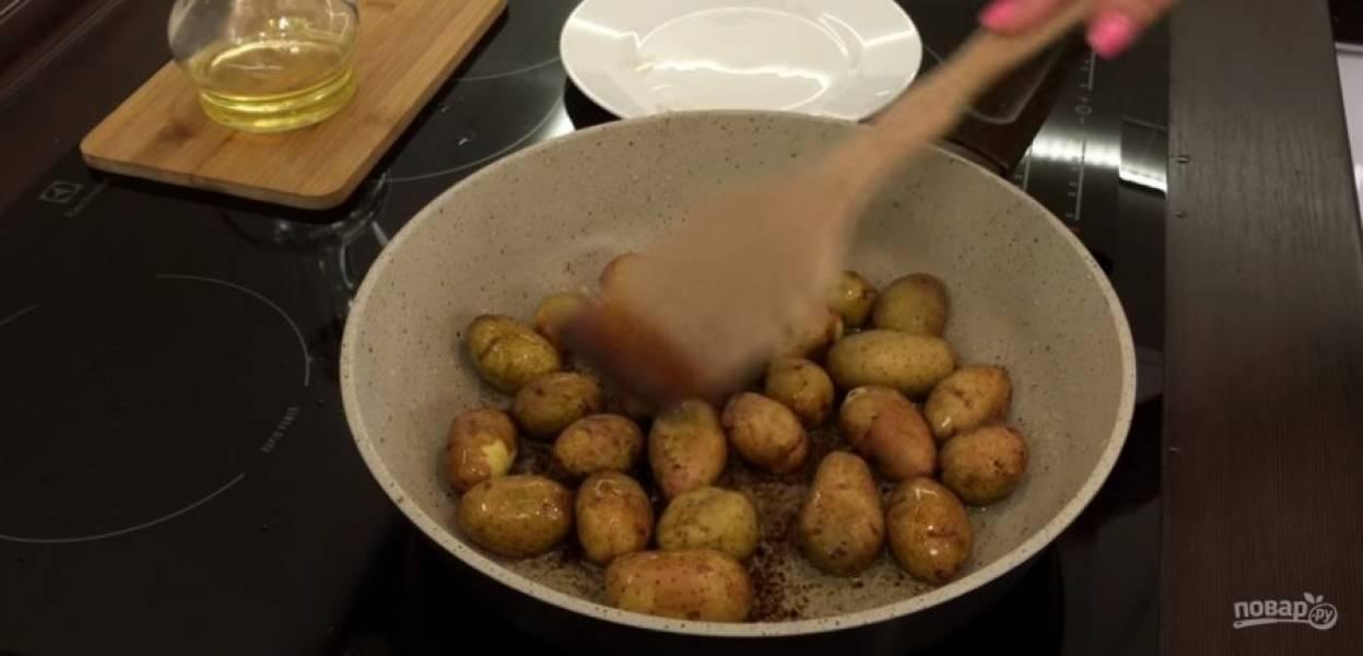 1. Картофель промойте под проточной водой и обсушите на полотенце. На разогретую сковороду вылейте растительное масло и соевый соус. На большом огне жарьте картофель 5 минут, постоянно помешивая.