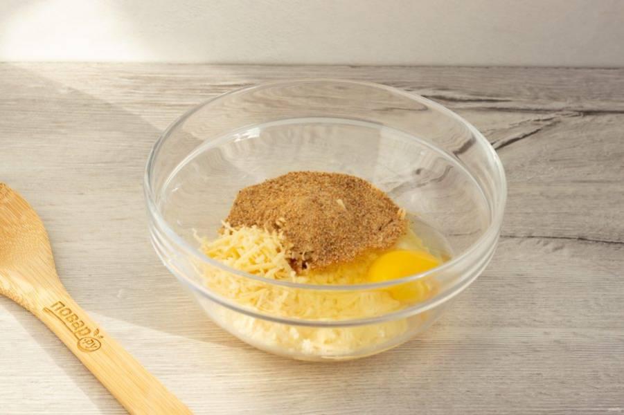 Сыр натрите на мелкой терке. Добавьте к сыру сырое яйцо и постепенно всыпайте панировочные сухари, пока масса не станет тестообразной.