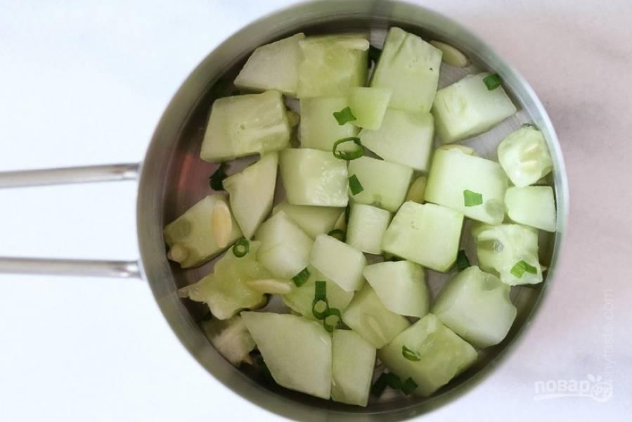 1.Вымойте и нарежьте небольшими кубиками огурцы, измельчите зеленый лук. В сотейник выложите огурцы и лук.