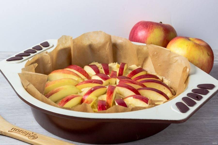 Яблоки нарежьте дольками и вдавите в тесто срезом вниз, как показано на фото.