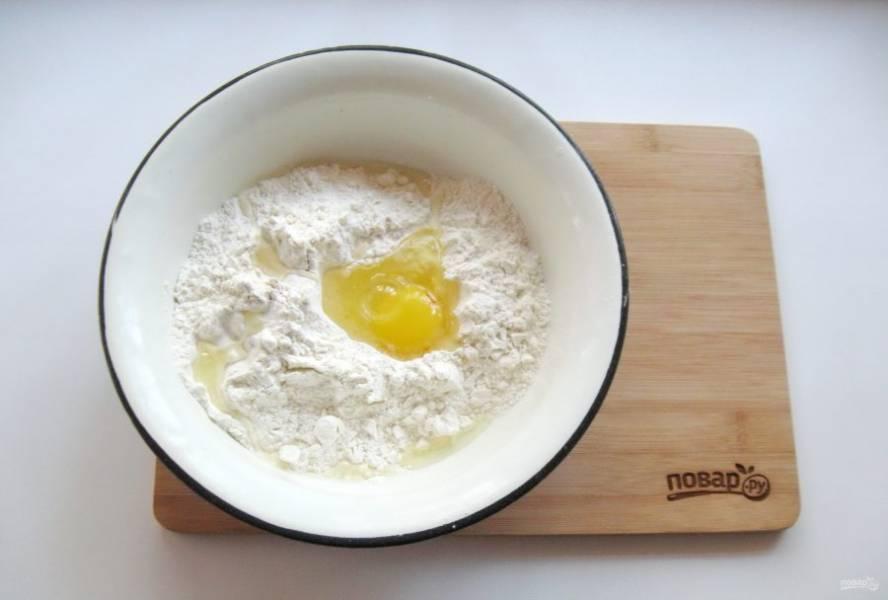 Приготовьте тесто для пельменей. В миску насыпьте муку, добавьте яйцо, соль и подсолнечное масло.