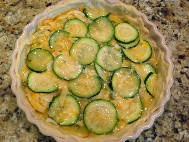 Смажьте тесто горчицей. Обжаренные овощи смешайте с массой из взбитых яиц и сыра. Добавьте специи. Выкладываем массу равномерно в форму.