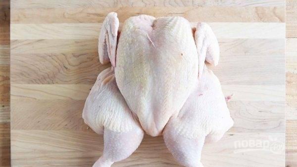 3.Переверните курицу и немного разложите ее. Сложите ноги так, чтобы они были повернуты внутрь, а большая часть курицы — вверх.