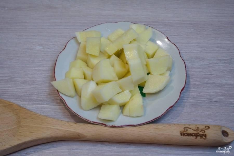Нарежьте картофель кубиками, добавьте его к курице в кастрюлю.