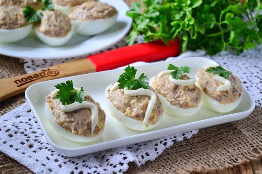 Подавайте фаршированные яйца полив майонезом и украсив зеленью. Приятного аппетита!