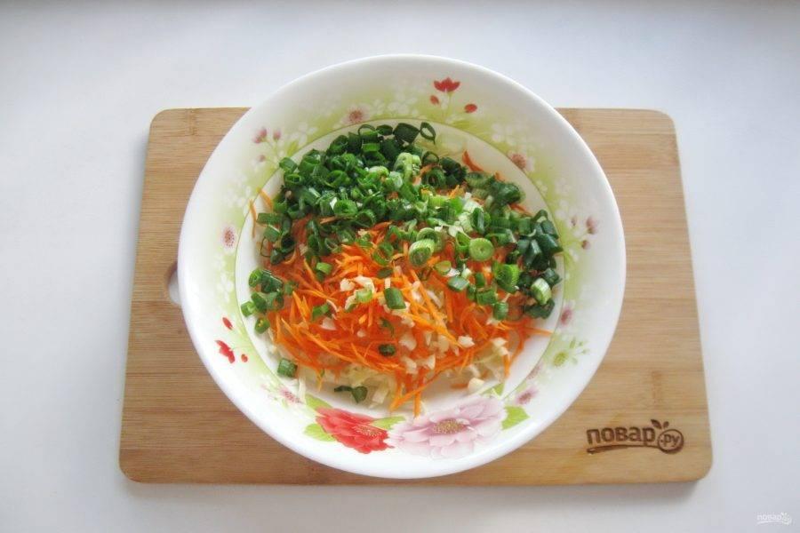 Зеленый лук помойте и мелко нарежьте. Выложите в салатник.