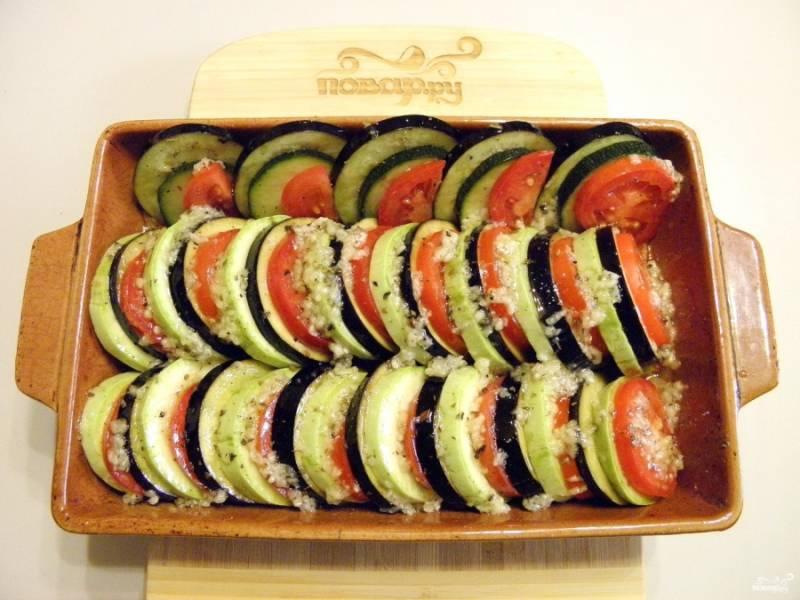 Овощи посолите по вкусу, выложите на соус, чередуя кабачок, баклажан и помидор. Сверху щедро полейте ароматным маслом с чесноком и травами. Накройте фольгой форму, отправьте её на 30 минут в духовку, температура — 180 градусов.