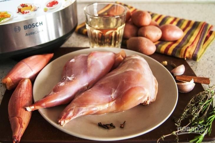Кролика промойте и обсушите. Лук почистите и крупно нарежьте. Картофель промойте, сделайте на нём надрезы с одной стороны.