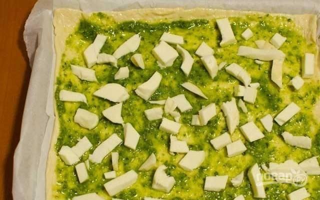 1. Противень устелите пергаментом и выложите тесто для пиццы, раскатанное в пласт. Сформируйте невысокие бортики, смажьте тесто небольшим количеством оливкового масла и соусом песто, посолите. Выложите измельченную моцареллу.