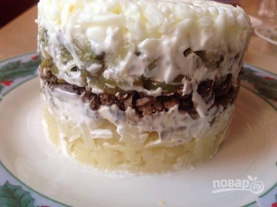 И формируем слоеный салат. Первый слой картофельный, смажем майонезом. Затем выкладываем лук и печень, смазываем. И дальше — огурцы, майонез, белок, майонез.