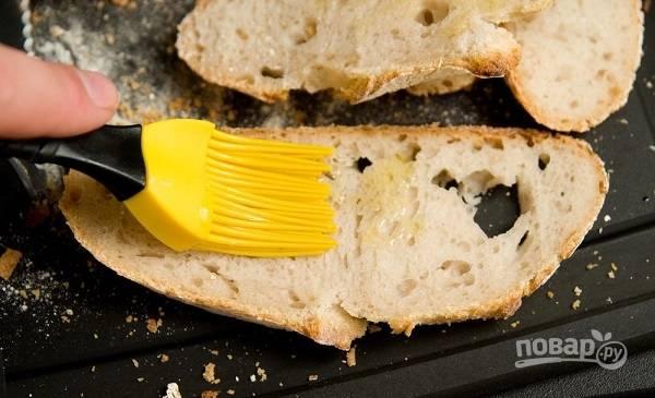 2. Нарежьте хлеб тонкими ломтиками, смажьте чуточкой масла.