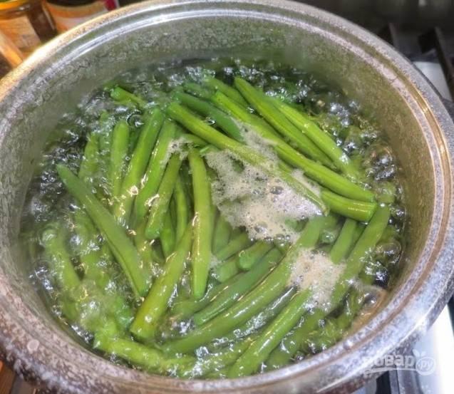 Вскипятите в кастрюле подсоленную воду, положите фасоль и варите 7-10 минут. Фасоль выложите в дуршлаг, часть отвара сохраните.