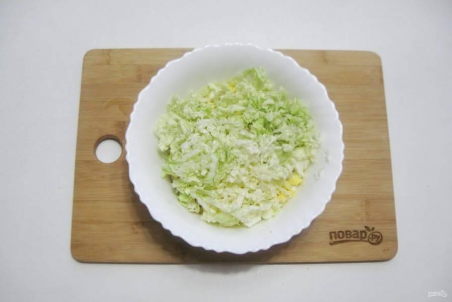Пекинскую капусту нарежьте тонкой соломкой. Выложите в салат.