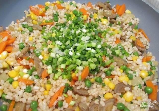 Затем выложите к овощам варёный коричневый рис и мелко рубленный зелёный лук. Обжаривайте рис с овощами ещё 5 минут. Ваше потрясающее блюдо готово. Подавайте рис жареный с овощами, украсив зеленью.