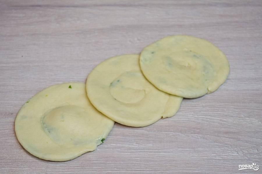 Пальцами или скалкой прокатайте тесто так, чтоб оно стало максимально тонким. Не порвите тесто, чтоб зелень не выбилась наружу. При обжаривании такая зелень будет гореть.