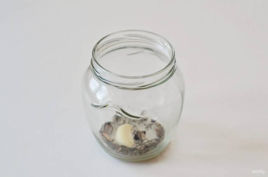 На дно чистой стерилизованной банки выложите сушеные стебли укропа, душистый перец и черный перец горошком, очищенный зубчик чеснока.